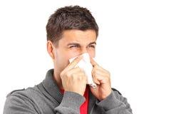 Hombre infectado que sopla su nariz en papel de tejido foto de archivo libre de regalías