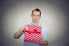 Hombre infeliz gruñón del trastorno que sostiene la caja de regalo roja muy descontentada Foto de archivo