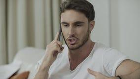 Hombre infeliz que habla el teléfono móvil en casa Grito enojado de la persona en el teléfono metrajes