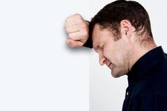 Hombre infeliz que se inclina en la pared Fotos de archivo