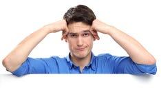 Hombre infeliz que se inclina en whiteboard Imágenes de archivo libres de regalías