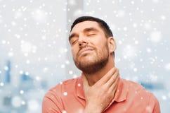 Hombre infeliz que sufre de dolor de la garganta sobre nieve Foto de archivo libre de regalías