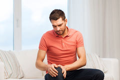 Hombre infeliz que sufre de dolor en pierna en casa Foto de archivo