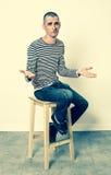 Hombre infeliz 30s con el pelo corto que discute y que se queja, sentándose foto de archivo