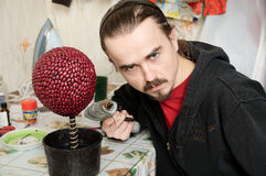Hombre ingenioso con el arma de pegamento que hace el árbol hecho a mano del topiary, afición casera de la artesanía de la decora Foto de archivo libre de regalías