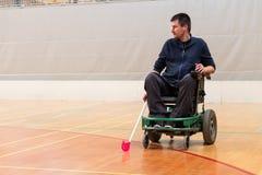 Hombre inhabilitado en una silla de ruedas el?ctrica que juega los deportes, hockey del powerchair IWAS - Silla de ruedas y amput imagen de archivo