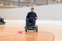Hombre inhabilitado en una silla de ruedas el?ctrica que juega los deportes, hockey del powerchair IWAS - Silla de ruedas y amput imagen de archivo libre de regalías
