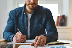 Hombre inidentificable que comprueba notas sobre el escritorio imagen de archivo libre de regalías