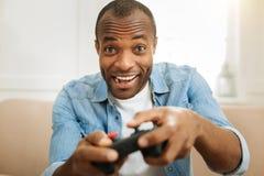 Hombre inspirado que relaja y que juega a juegos Fotografía de archivo
