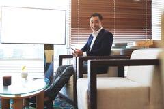 Hombre inteligente alegre que se sienta con la almohadilla táctil cerca de la pantalla vacía con el espacio de la copia para su c Imágenes de archivo libres de regalías