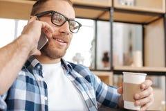 Hombre inteligente positivo que sostiene una taza plástica con café Imagen de archivo libre de regalías