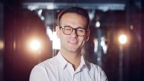 Hombre inteligente sonriente en vidrios en un cuarto con los flashes de paredes ligeras y transparentes metrajes