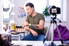 Hombre interesado comunicativo que tiene diversos productos de maquillaje en la tabla imagenes de archivo