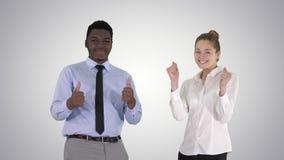 Hombre internacional y mujer sonrientes felices que muestran los pulgares para arriba en fondo de la pendiente metrajes