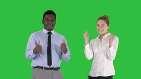Hombre internacional y mujer sonrientes felices que muestran los pulgares para arriba en una pantalla verde, llave de la croma almacen de video