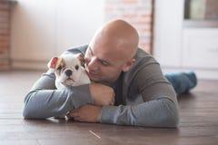 Hombre intrépido hermoso con el dogo del inglés del perrito Fotografía de archivo libre de regalías