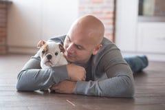 Hombre intrépido hermoso con el dogo del inglés del perrito Fotos de archivo libres de regalías