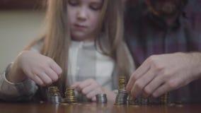 Hombre irreconocible en camisa y poca muchacha concentrada que se sienta en la tabla que cuenta monedas cerca para arriba Padre y metrajes