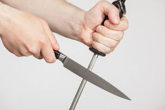 Hombre irreconocible que afila un cuchillo grande fotografía de archivo libre de regalías