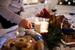 Hombre irreconocible que enciende velas en la guirnalda de la Navidad Foto de archivo