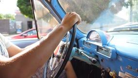 Hombre irreconocible que lleva a cabo las manos en un volante e impulsiones un coche retro en la carretera nacional en día de ver metrajes