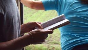 Hombre irreconocible que se coloca cerca de puerta abierta del tren móvil y que lee el libro interesante Montar a caballo joven d metrajes