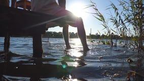 Hombre irreconocible que se sienta al borde de un embarcadero de madera en el lago y pies de balanceo en el agua Individuo joven  almacen de metraje de vídeo