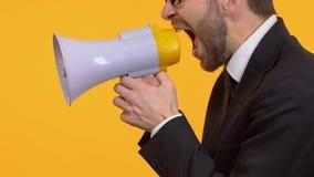 Hombre irritado que grita en el megáfono, campaña de protesta, elección, lado-vista almacen de video