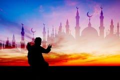Hombre islámico que ruega rezo musulmán en el tiempo crepuscular Imágenes de archivo libres de regalías