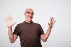 Hombre italiano europeo en un humor del pánico que agita sus brazos En camisa y vidrios marrones Imagen de archivo