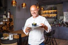 Hombre italiano hermoso calvo con una barba en el cocinero uniforme blanco en un restaurante que presenta con una sonrisa dentuda fotografía de archivo libre de regalías