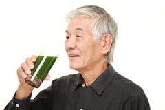 Hombre japonés mayor con el jugo vegetal verde Imagen de archivo libre de regalías