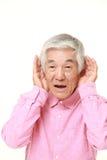 Hombre japonés mayor con la mano detrás del oído que escucha de cerca Fotografía de archivo