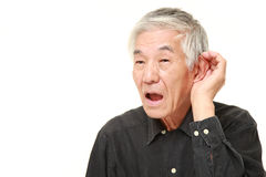 Hombre japonés mayor con la mano detrás del oído que escucha de cerca Imágenes de archivo libres de regalías