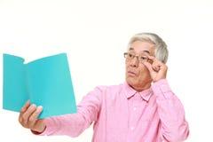 Hombre japonés mayor con presbiopía Foto de archivo
