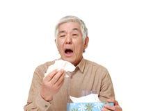 Hombre japonés mayor con una alergia que estornuda en tejido Imagen de archivo libre de regalías