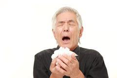 Hombre japonés mayor con una alergia que estornuda en tejido Fotos de archivo