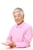 Hombre japonés mayor que comprueba su pulso Foto de archivo libre de regalías