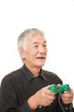 Hombre japonés mayor que disfruta de un videojuego Fotos de archivo libres de regalías