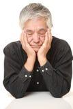 Hombre japonés mayor que duerme en la tabla Imagen de archivo