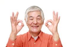 Hombre japonés mayor que muestra la muestra perfecta Foto de archivo libre de regalías