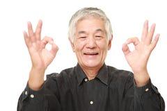 Hombre japonés mayor que muestra la muestra perfecta Foto de archivo