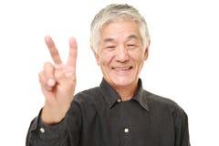 Hombre japonés mayor que muestra una muestra de la victoria Imágenes de archivo libres de regalías