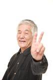 Hombre japonés mayor que muestra una muestra de la victoria Foto de archivo libre de regalías