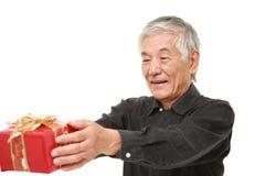 Hombre japonés mayor que ofrece un regalo Foto de archivo libre de regalías