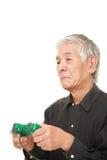 Hombre japonés mayor que pierde jugando al videojuego Fotos de archivo