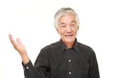 Hombre japonés mayor que presenta y que muestra algo Fotografía de archivo