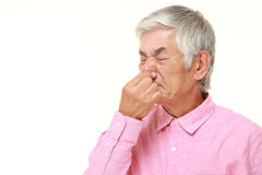 Hombre japonés mayor que se sostiene la nariz debido a un mún olor Imagen de archivo libre de regalías