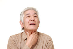 Hombre japonés mayor que tiene dolor de la garganta Foto de archivo