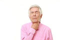 Hombre japonés mayor que tiene dolor de la garganta Foto de archivo libre de regalías